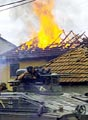 A German KFOR tank in front of a burning Serb house in Kosovo