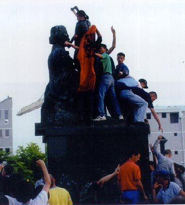Albanian crowd with a flag and axes on the monument of Vuk Karadzic